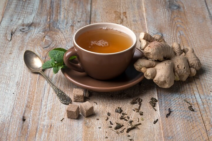 Cup Of Ginger Tea Next To Ginger Root