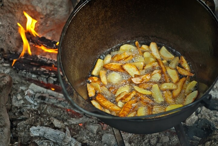 French Fries Cooking In Pot Over Fire