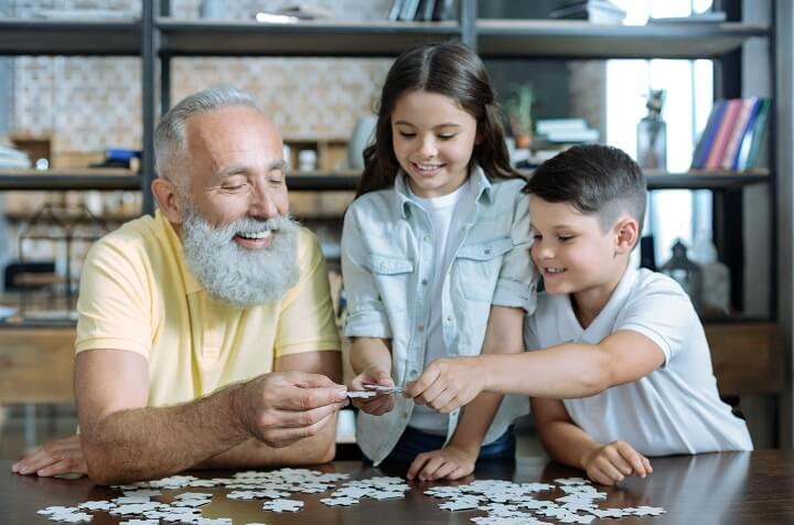 Grandfather and Grandkids Working On Puzzle