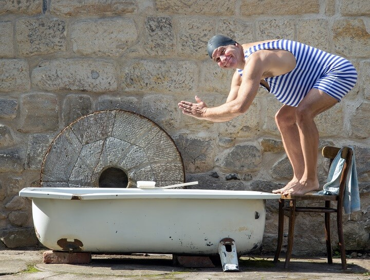 Man In Swimsuit Jumps Into Outdoor Bathtub