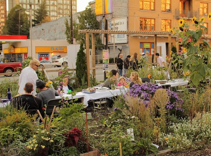 People Eating In Community Garden