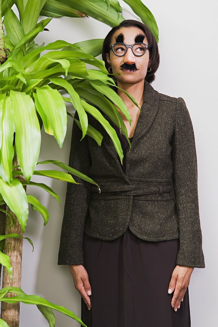 Woman In Disguise Behind Plant